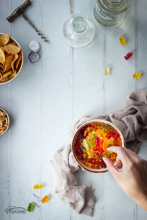 Flat lay view of a hand reaching for vodka gummy bears in a bowl over a light brown linen napkin. There is also a bowl of crisps, a bowl of cashew nuts, 2 bottles of spirits, a cork screw, 2 bottle tops, 2 corks and gummy bears in the background. Set over a pale green wood effect backdrop.