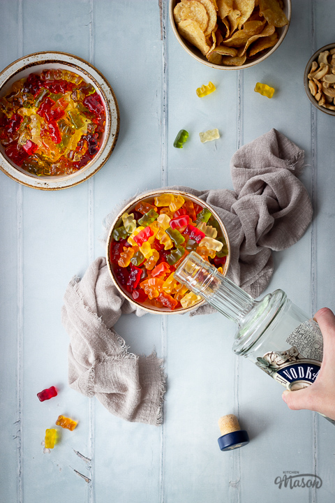 Flat lay view of vodka gummy bears in a bowl with a hand pouring vodka into them, set on a light brown linen napkin. Set on a pale green wood effect backdrop, there is also a bowl of crisps, a bowl of cashew nuts, another bowl of vodka gummy bears set on a plate, a bottle top and gummy bears in the background.