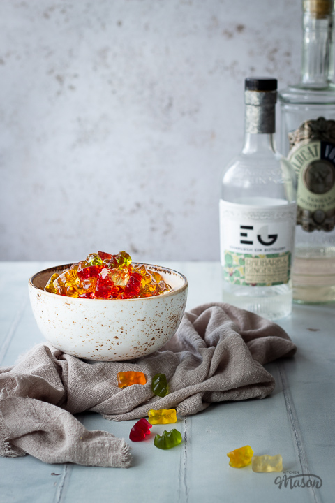 Front view of vodka gummy bears in a white bowl over a light brown linen napkin. Set over a pale green wood effect backdrop, there are also 2 bottles of spirits in the background and scattered gummy bears in the foreground.