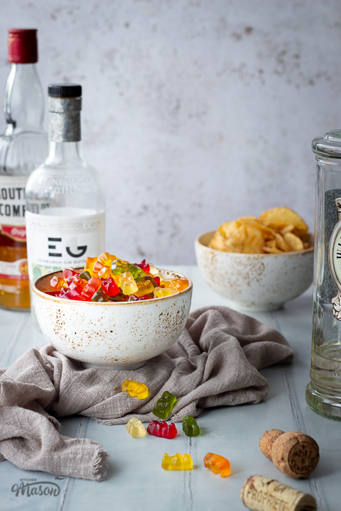 Front view of vodka gummy bears in a white bowl over a light brown linen napkin. Set over a pale green wood effect backdrop, there are also 2 bottles of spirits and a bowl of crisps in the background and a bottle of vodka, a cork and scattered gummy bears in the foreground.