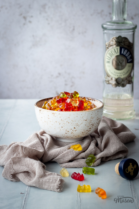 Front view of vodka gummy bears in a white bowl over a light brown linen napkin. Set over a pale green wood effect backdrop, there is also a bottle of vodka in the background and a bottle cork and scattered gummy bears in the foreground.