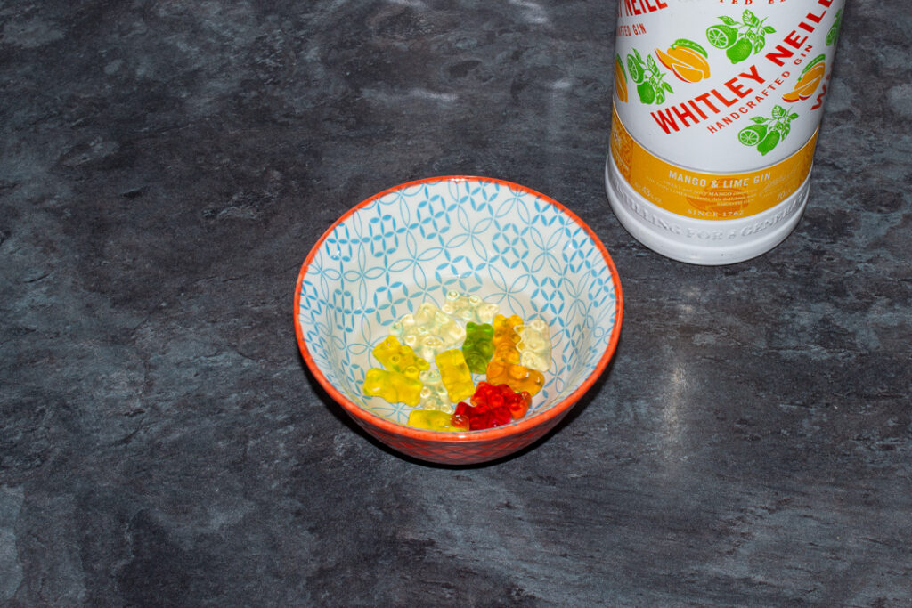 Gummy bears covered with mango and lime gin in a bowl on a kitchen worktop. There's a bottle of mango and lime gin in the background.