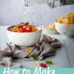 Front view of vodka gummy bears in a white bowl over a light brown linen napkin with a hand pouring vodka into them. Set over a pale green wood effect backdrop, there is also a bowl of crisps and a bowl of cashews in the background, and scattered gummy bears in the foreground. A test overlay says 'how to make vodka gummy bears'