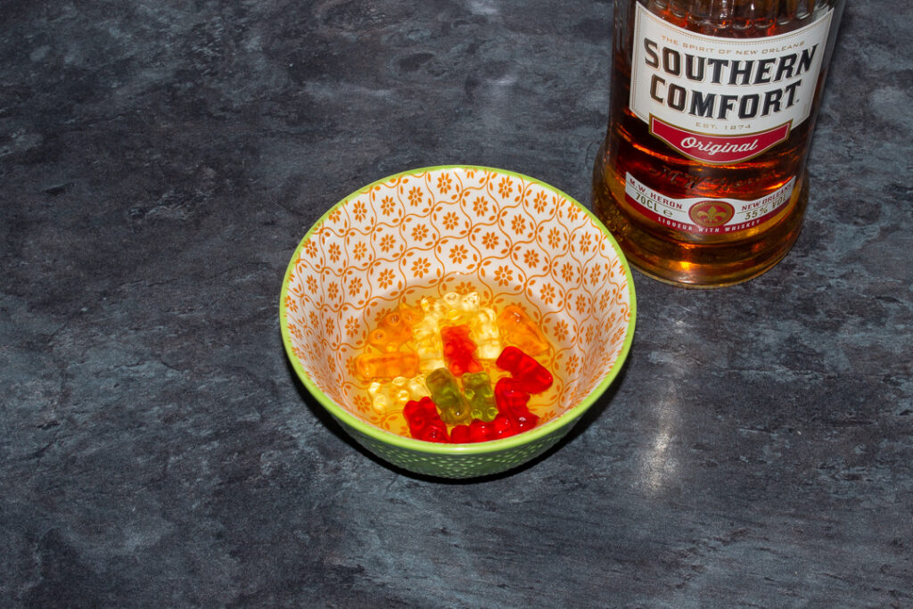 Gummy bears covered with Southern Comfort in a bowl on a kitchen worktop. There's a bottle of Southern Comfort in the background.