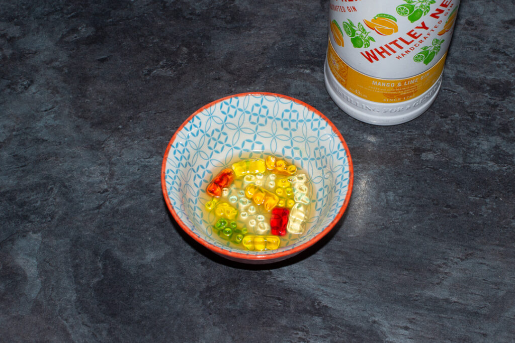 Gummy bears soaked in mango and lime gin in a bowl on a kitchen worktop. There's a bottle of mango and lime gin in the background.