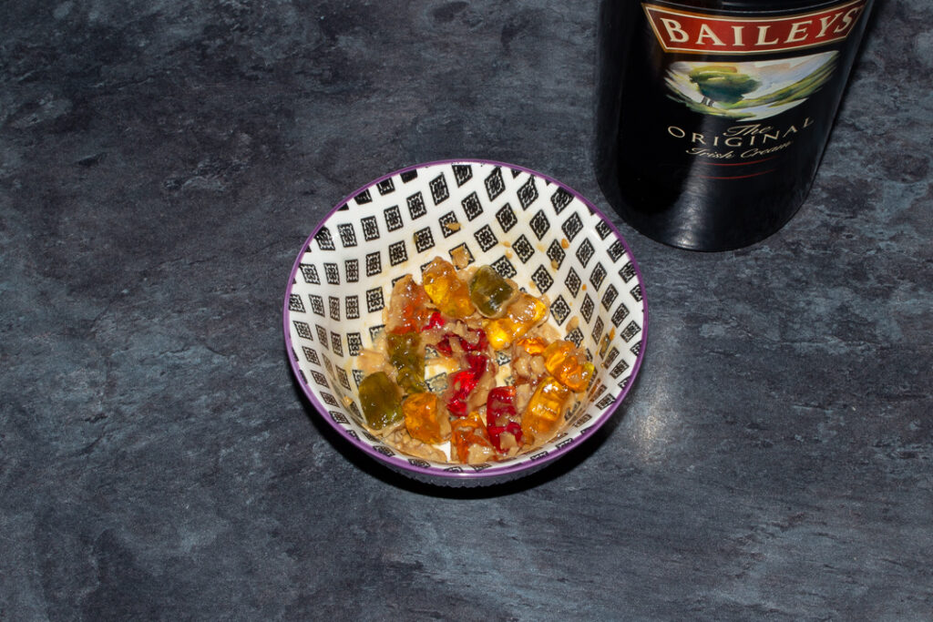 Gummy bears soaked in Baileys in a bowl on a kitchen worktop. There's a bottle of Baileys in the background.